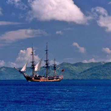 The Bounty sails off Raiatea, French Polynesia (Tahaa is in the background), after her stint as a Hollywood star. The Bounty movie had been shot on Moorea shortly before this photo was taken.