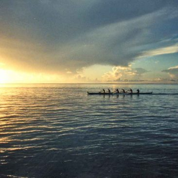 Tahitians paddling their va'a (outrigger) as the sun sets under a tropical sky.