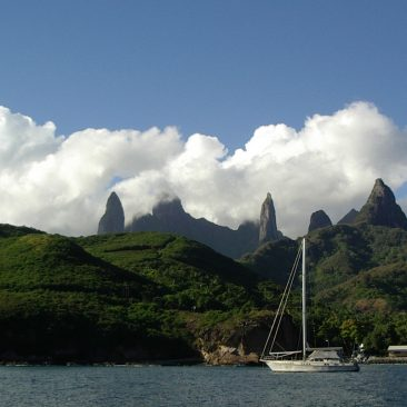 "A Swiss yacht anchored nearby off the beautiful, brooding, heavy ""mana"" island of Ua Pou, Marquesas."