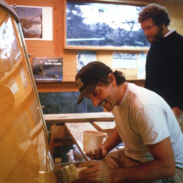 A master with paint (and varnish), Jimmy Raun Byberg puts the finishing touches on Shanachie's clear stern as Chucker Burgess looks on