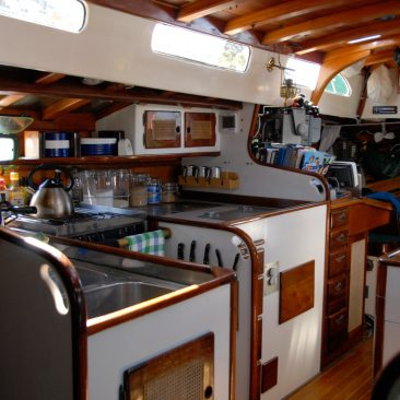Galley view, looking aft towards nav station, engine cabinet, and nav bunk, starboard side