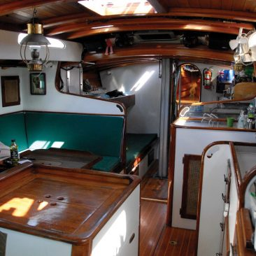 View forward, settee on port, galley on starboard, midship bunks visible beside mast